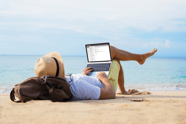 Man lying on a beach writing a story for the Pegasus Rental cars blog