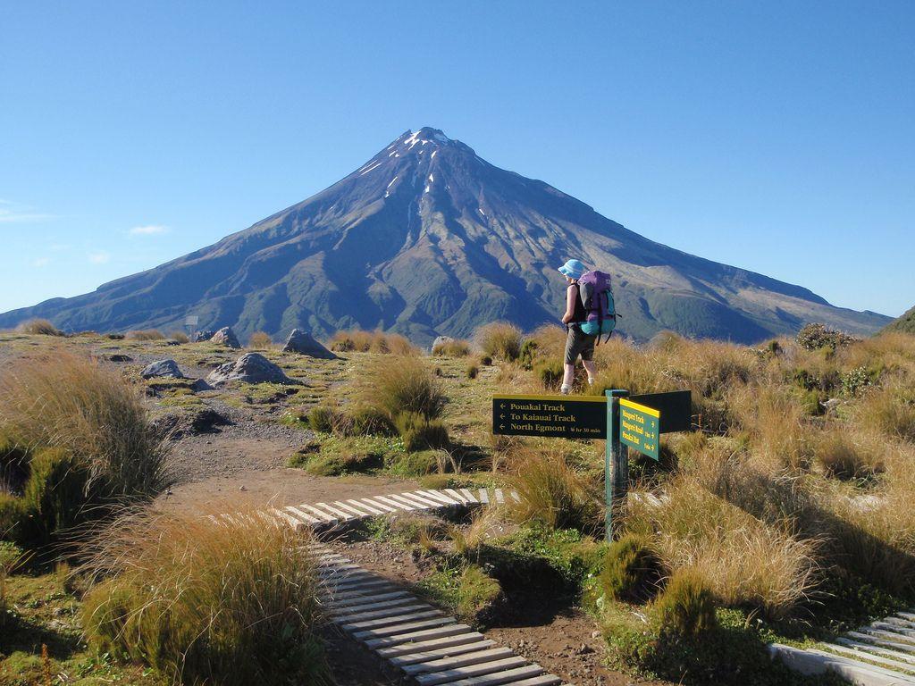 A hiker surveys the scenery looking towards Mt Taranaki