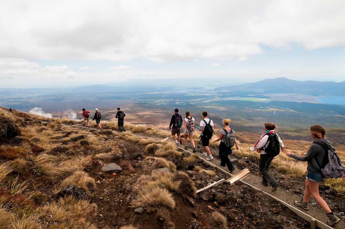 Hikers traversing the Tongariro Alpine Crossing In Ruapehu