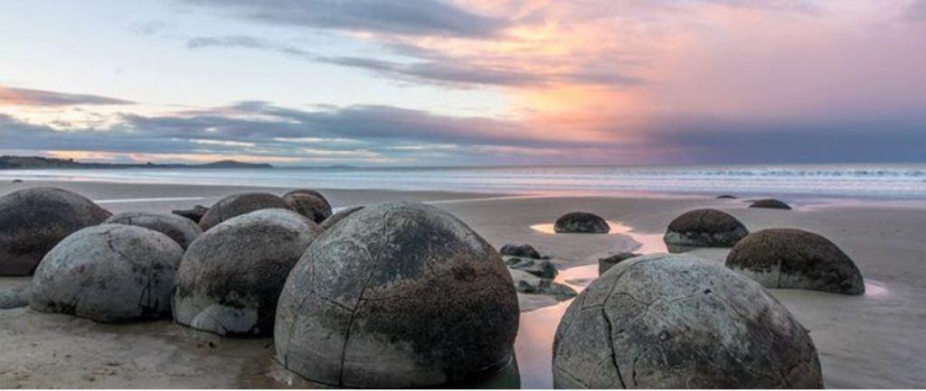 boulders along the Moeraki Boulders Beach during sunrise.