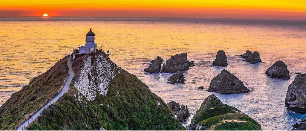 Sunset at Nugget Point Lighthouse over looking ocean.