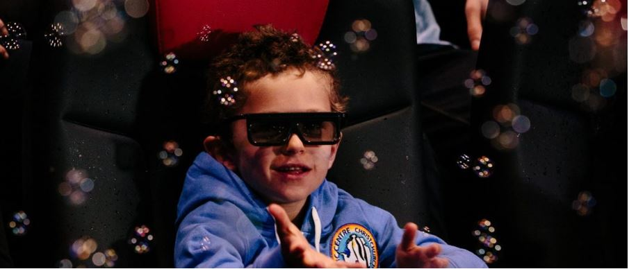 a kid with 3D glasses playing with bubbles at the 4D theater
